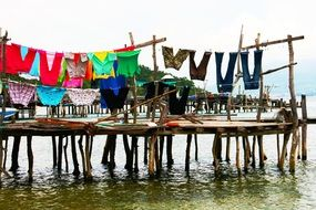 bright clothes drying on line above wooden pier