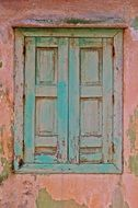 weathered green shutters on window in old pink facade, greece, samos