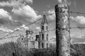 ruined church behind barb wire fence, russia, siberia