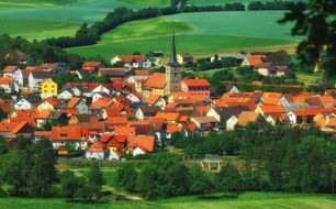 scenic old town with red roof buildings in green countryside, germany, bavaria, burglauer