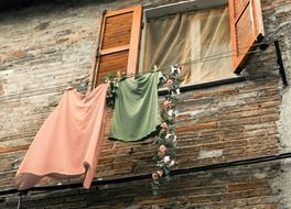 clothes on line at window on old brick facade