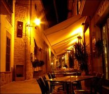 open air restaurant on narrow street of old town at night