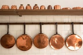 old georgian style copper pans and baking moulds on kitchen