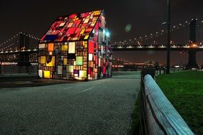 colorful glass house in view of bridge at night, usa, manhattan, new york city