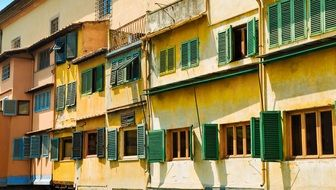 green shutters on yellow facade at sunny day