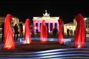 ladies in red garments at brandenburg gate, light show, germany, berlin