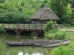 19th century village house and boats on water at bridge, open air museum, poland
