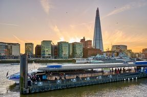 ship at pier in view of the shard building in city skyline, uk, england, london