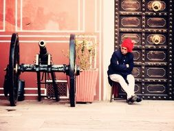 old man in traditional clothing sits at wall of fort beside of cannon, india, rajasthan, mughal