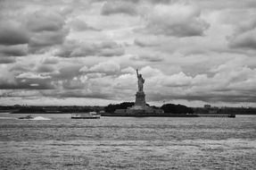 statue of liberty at clouds, distant view from sea, usa, manhattan, new york city