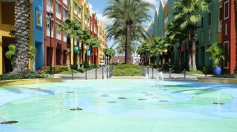 fountain on street and palm trees at colorful houses, netherlands, curacao, willemstad
