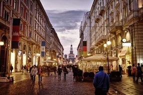 people on street of old city at evening, italy, milan