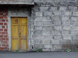 yellow wooden door in old facade