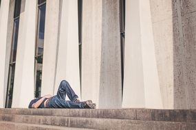 man in jeans lying on stone steps at facade