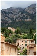 old village buildings at foggy mountains, spain, mallorca, deia