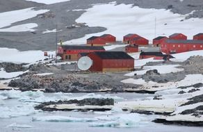 red buildings of argentina's antarctica station on frozen coast, south pole