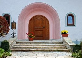 wooden door in arched doorway above stairs, old beautiful stone facade