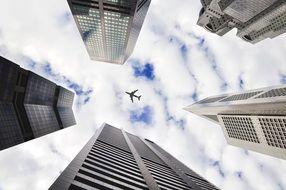 airplane against the clouds between the towers of buildings