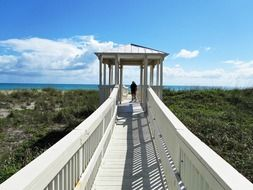 people on wooden walkway at ocean, usa, florida