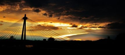 silhouette of suspension bridge at sunset sky