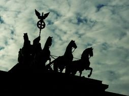 silhouette of quadriga atop brandenburg gate at clouds, germany, berlin