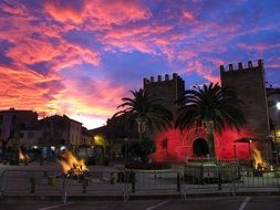 fires on square at town gate under awesome sunset sky, spain, mallorca, alcudia abendstimmung