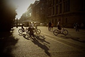 people with bicycles on street in town at summer sunset