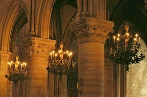wrought iron chandeliers under gothic ceiling
