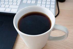 coffee cup at keyboard on desk