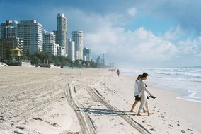 barefoot people walking to water on beach in view of modern city