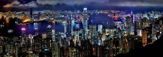 night skyline of illuminated metropolis at water, china, hong kong