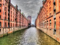 old red brick buildings at channel under grey clouds, germany, hamburg, speicherstadt
