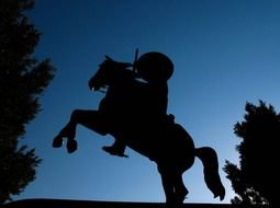 silhouette of cowboy statue at night sky, mexico