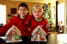 two boys and two gingerbread houses on the background of the Christmas tree