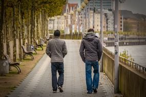two young men walking on rhine waterfront, germany, düsseldorf