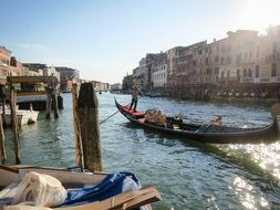cityscape with people in gondola on canal, italy, venice