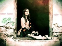 young pretty girl sits in doorway of old ruined house