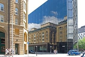 mirroring of old building on glass modern facade in city, uk, england, london