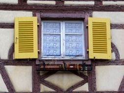 window with yellow shutters on facade of truss building, france