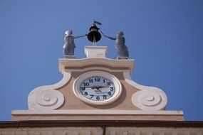 clock with metal figures on top of building