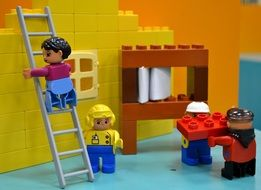 construction workers at wall, lego building blocks toy installation