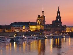 dusk skyline with tourist boats on water at cathedral, germany, dresden