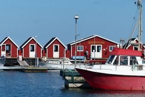 red fishermen's cabins and boat at pier, scandinavia