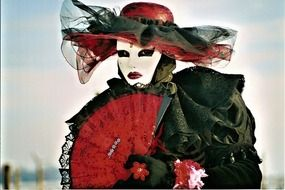 black dressed person in woman mask with red fan
