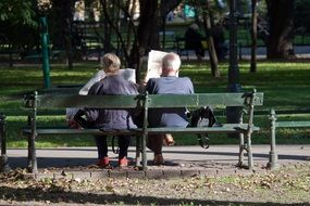 people reading newspapers on bench in park, poland, krakow
