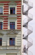 man on emergence spiral staircase at facade, germany, berlin
