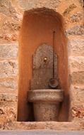 ancient stone fountain on facade, spain, mallorca