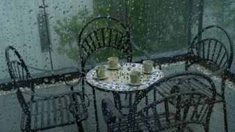 armchairs and round table with cups on balcony at rain