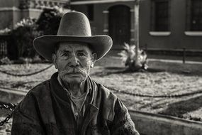 black white photo aged hat man house trees backgraund guatemala