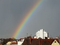rainbow at sky above city after rain